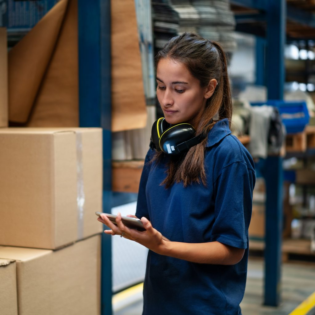 Female warehouse worker updating the stock on mobile phone app. Woman in uniform working in a factory warehouse.