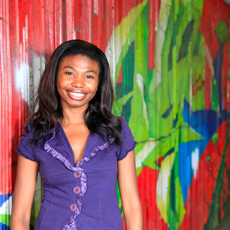 Young African woman standing in front of mural