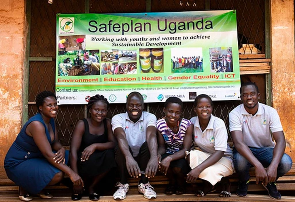 Six young adults posing in front of banner