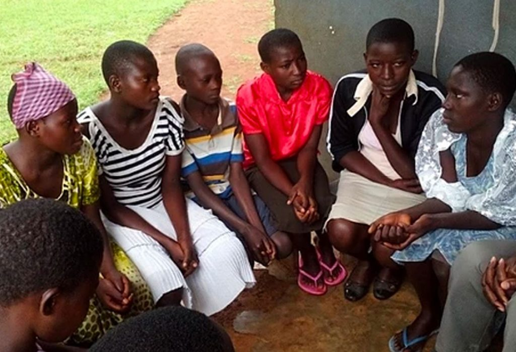 Group of young people in discussion, sitting in circle