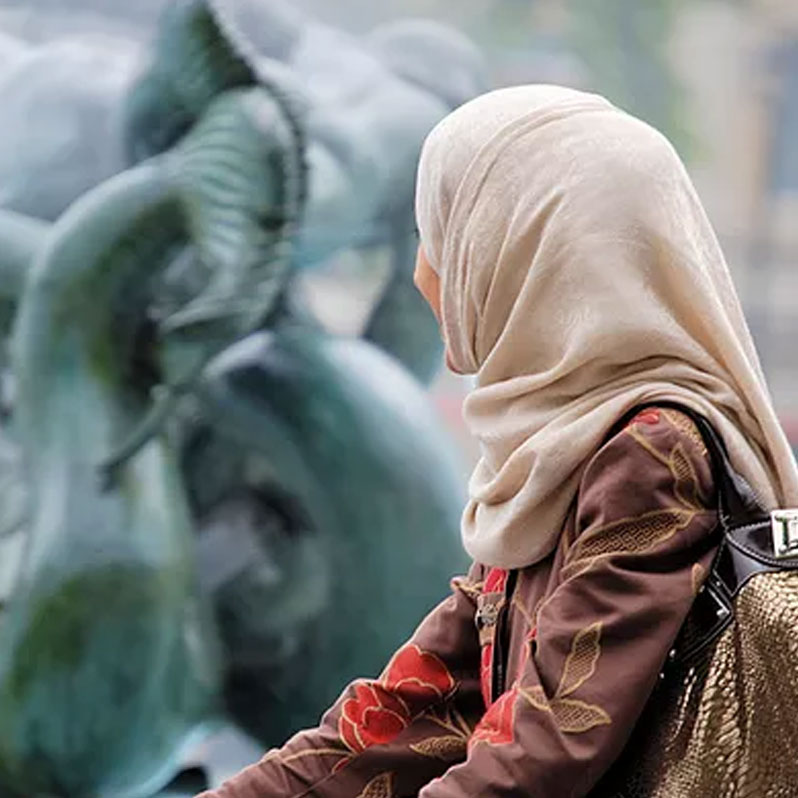Woman in head scarf looking at statue