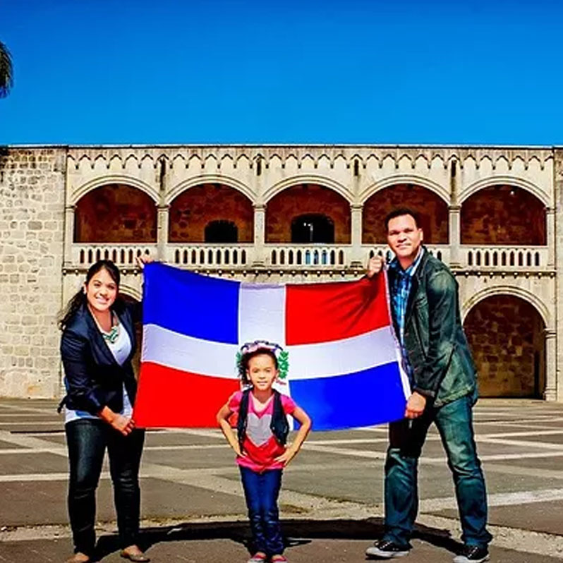 Woman, man, and child posing with flag of the Dominican Republic