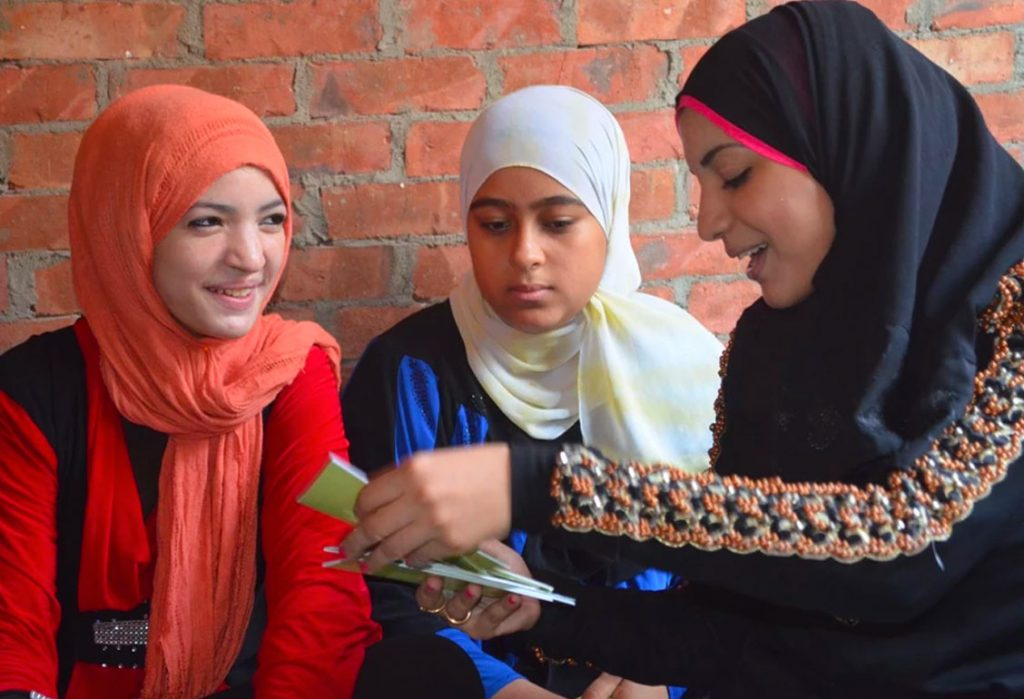 three young women reading and talking