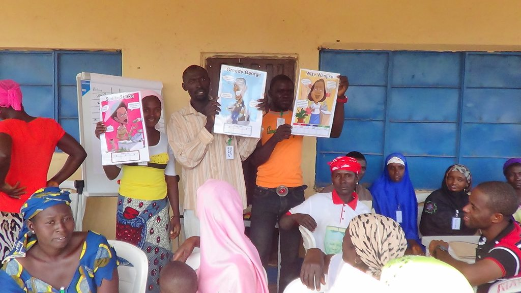 Three adult Nigerian students standing in front of a class of adult students learning microenterprise curriculum called Microenterprise Fundamentals. They are holding up learning materials.